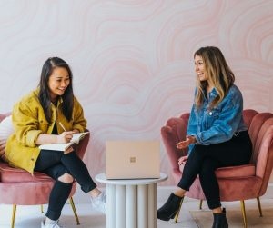 Two Women Freelancers Sitting On Chairs Talking Business of Creativity