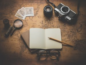 Brown Map Table with Open Notebook, Compass, and Camera - Business of Creativity Article on Attracting Freelance Clients