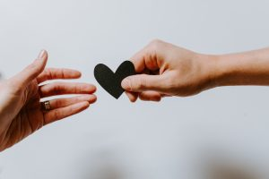 Two Hands, White Background, Passing a Black Heart - Business of Creativity Article on Attracting Freelance Clients