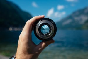 Hand Holding a Camera Lens Looking at a Landscape - Business of Creativity Article on Freelance Clients